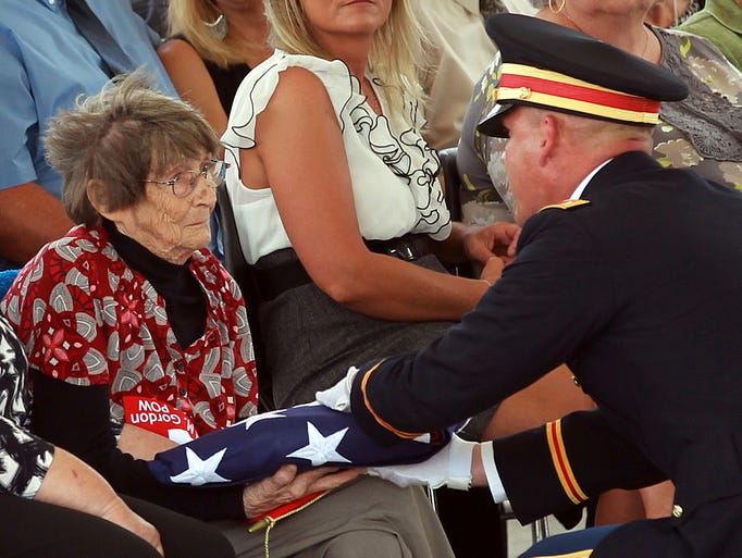An Army officer presents Dorothy Gayhart, 80, the flag from the casket of her brother, Sgt. Paul M. Gordon, of Crittenden. who died in a prisoner of war camp in 1951 during the Korean War.  The remains were recently identified by the Armed Forces DNA Identification Laboratory.  He was buried at Veterans Cemetery North near Williamstown.
