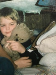 A young Ryan Reynolds holding his Raggedy Teddy.