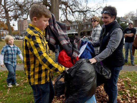 Tristan Rankin, 9, left, pulls coats out of a plastic