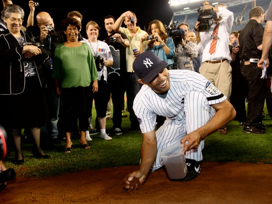 New York Yankees closer Mariano Rivera gathers dirt from the pitcher's mound after the final game at the old Yankee Stadium in 2008 as Naomi Gandia (far left) looks on.