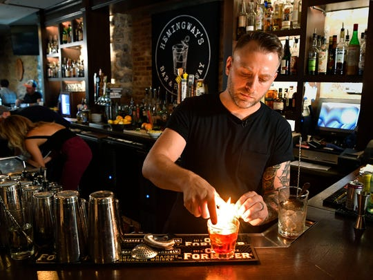 "Christopher Weber, co-owner of Hemingway's Bar & Hideaway puts the finishing touches on a ""Steve McQueen."""