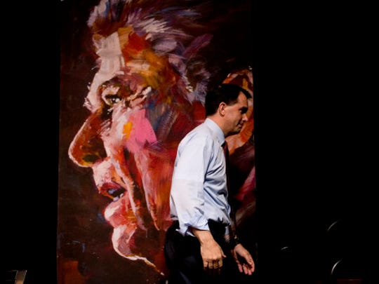 Republican presidential candidate Wisconsin Gov. Scott Walker walks past a portrait of former President Ronald Reagan as he leaves the stage after speaking at the RedState Gathering Saturday, Aug. 8, 2015, in Atlanta.