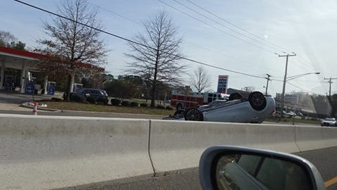 A car lies overturned on Route 37 near Commonwealth Boulevard in Manchester.