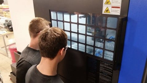 Arrowhead students look into the new CNC mill machine at the DEMC.