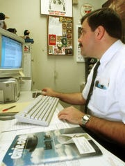 In this 1999 file photo, Steve Meilahn, then of the Everest Police Department, researches a case of credit card fraud.