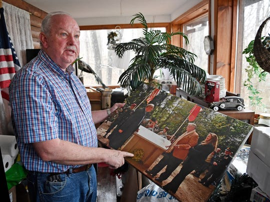 Retired Col. Gerald York shows a photo taken as he and his father attended a ceremony near Chatel-Chéhéry, France, where a memorial to his grandfather now stands.