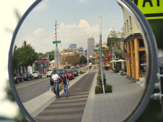 People walking north on the Cultural Trail along South Virginia Ave., with downtown reflected in a safety mirror,  Friday July 19, 2013.