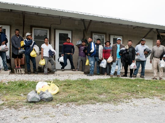"""Migrant workers pose for a photo after getting their care packages from Fruitbelt Farmworker Christian Ministry. """"The idea is to get into the camps and let the guys know, who in many places are marginalized, that there are people that care for them,"""" said Reverend Roddy Runyan, director of the ministry."""