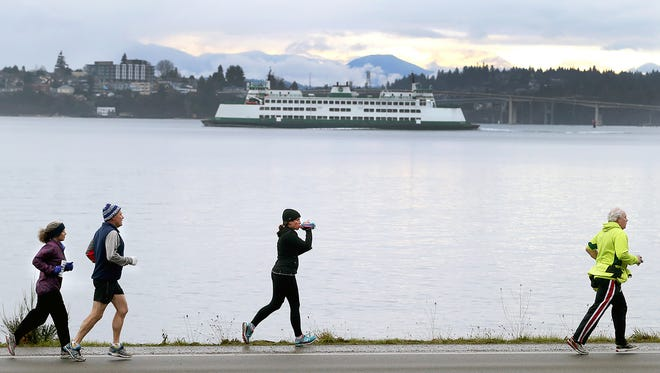 Yukon Do It! half marathon runners run along Beach Drive in Port Orchard as the Bremerton ferry passes on it's way to dock on a cold gray Saturday morning.