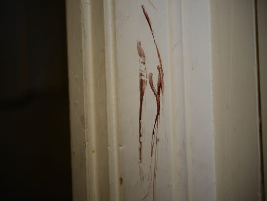A dark red stain in a doorframe in the lobby of 184