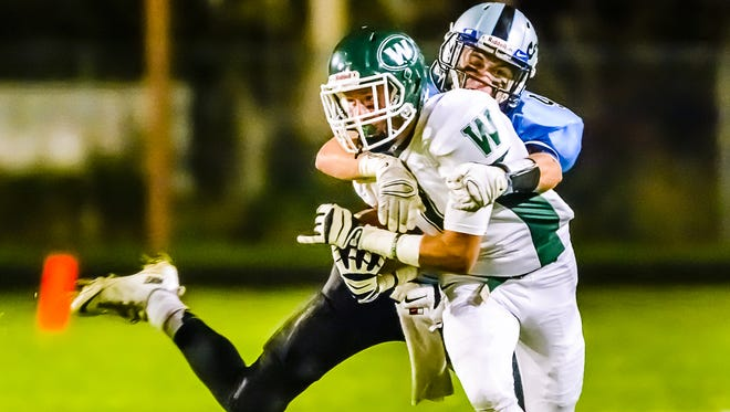 Connor Rucinki, background, of Lansing Catholic wraps up Montana Reagan of Williamston during their game Friday October 10, 2014 at Holt Junior High School in Holt.  KEVIN W. FOWLER PHOTO