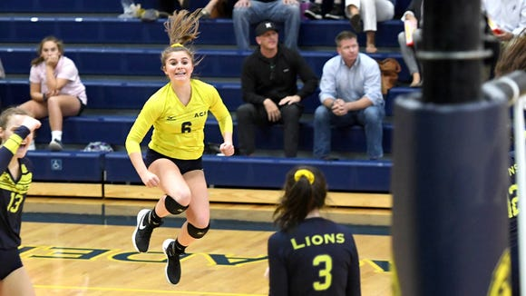 Asheville Christian Academy libero Sophie Whalen leaps into the air to celebrate a point during the Lions' NCISAA-2A State semifinal game against Caldwell Christian Academy on Tuesday, Oct. 24, 2017. The Lions defeated the Eagles 25-23, 25-22, 23-25, 25-17.