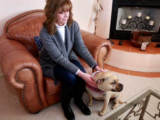 Mary Jane Washburn sits with her dog, Katie, on Wednesday at her home in Farmington. Katie will be inducted into the New Mexico Pet Hall of Fame for alerting her owners of a kitchen fire.