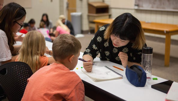 A Korean student helps local children with math in