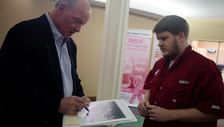 """Marty Lyon, former NFL and Alabama football player, signs a picture for Jason Hill, right, during a silent auction and screening of the documentary """"Climb for Kevin"""" on Friday, Jan. 15, 2016 in Prattville, Ala. The movie details the struggle Kevin Turner faces with ALS. Turner was a standout fullback at Prattville High and went on to the University of Alabama before making it to the NFL playing for the New England patriots before wrapping up his career with the Philadelphia Eagles. The screening is a fundraiser for the Kevin Turner Foundation."""