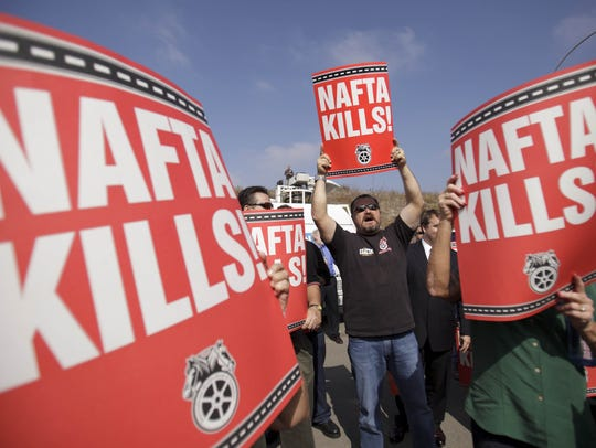 Teamsters union members hold signs opposing the North