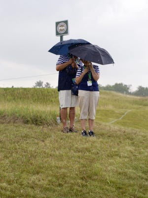 Fans hunker under their umbrellas during a rainy spell Aug. 10, at Whistling Straits.