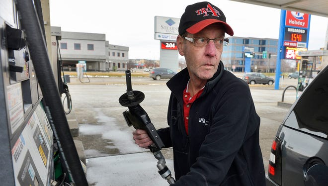 Michael Brumback of Minnetonka fills up his SUV with $1.55 gas Sunday afternoon, Feb. 7 at the Holiday convenience store on Waite Avenue and Second Street South in Waite Park. Brumback says even though prices are low, he still tries to keep the number of miles he drives to a minimum.