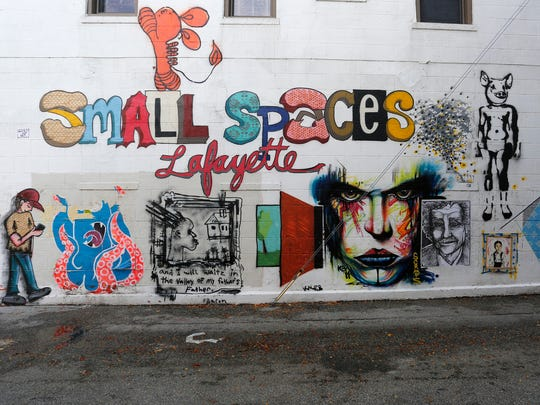 """The work of several artists taking part in """"small spaces: Lafayette"""" is displayed on the side of Bernadette's Barbershop in downtown Lafayette."""