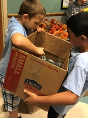 Landon Ward and Tristan Smith work together to get donations ready for delivery to the Treasure Coast Food Bank.