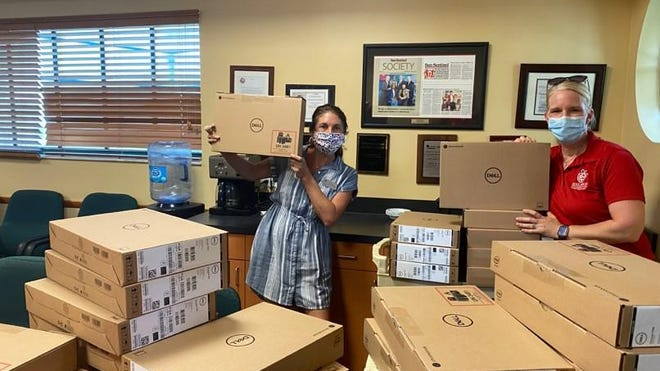 Jessica Hall, left, director of Achievement Centers for Children & Families Foundation, and Catherine Blomeke, of the Education Foundation of Palm Beach County, organize shipments of new Dell Chromebooks for Achievement Center youth.