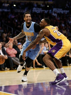 Los Angeles Lakers' Tarik Black, right, knocks the ball out of the hand of Denver Nuggets' Wilson Chandler during the first half of an NBA basketball game, Tuesday, Jan. 31, 2017, in Los Angeles. (AP Photo/Jae C. Hong)