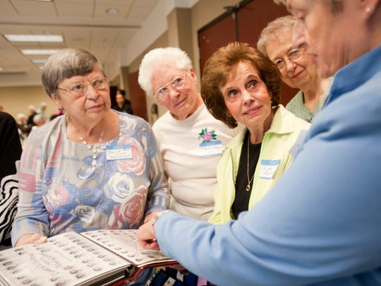 From left to right, class of 1960 graduates of the E.W. Sparrow School of Nursing Janice Hettinger, Margaret Sitterson, Ruth Spagnuolo, Kaye Harwood and Winnie Beeman look at class photos on Saturday, May 14, 2016 at the MSU University Club for the 95th, and final, reunion. The school operated from 1901 until 1961 in a building next to Sparrow, on Michigan Avenue. It graduated 1,017 nurses.