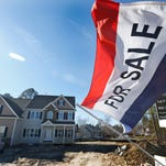 A flag advertising a newly built home for sale