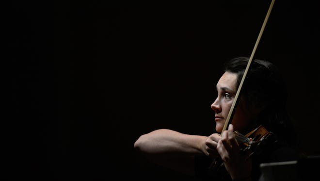 Sarah Larsen gazes out at an empty Weidner Center as she prepares to start rehearsal on her solo piece with the Green Bay Symphony Orchestra as they practice for their farewell performance at the Weidner Center for the Performing Arts on the UW-Green Bay campus on Thursday.