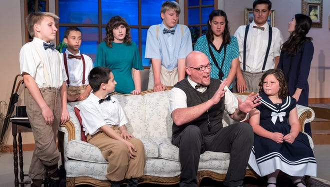 "Cliff Ayers, center, talks with youth in the cast for Encore Theatre's production of ""Cheaper by the Dozen"""