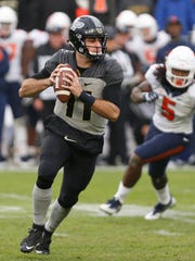 Purdue quarterback David Blough rolls out to pass in