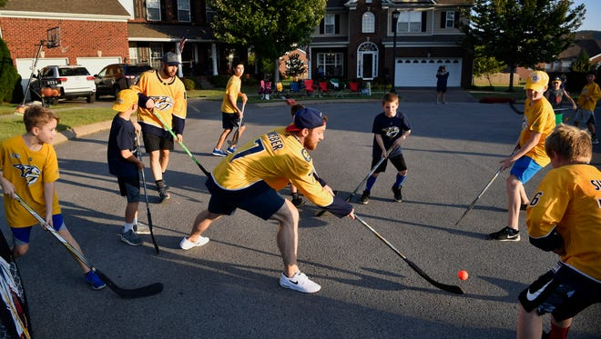 Predators player Yannick Weber reaches for the ball as he and Nick Bonino play street hockey with kids from a neighborhood in Nolensville that won a contestWednesday Oct. 11, 2017, in Nolensville, TN