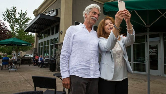 Sam Elliott (left) poses for a photo with fan Ginger Balazs outside a coffee shop in north Eugene.