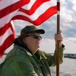 """Michael Moore plants flags in overseas nations in the documentary """"Where to Invade Next."""""""