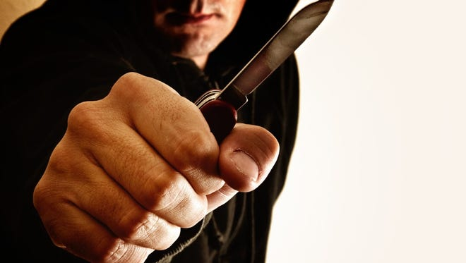 Stock image of a man holding a knife.