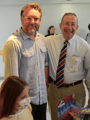 """Colin Trevorrow, the director and co-writer of the hit movie """"Jurassic World,"""" joins Dr. Lewis First, chief of pediatrics at The UVM Children's Hospital as he donates toys from the film to patients."""
