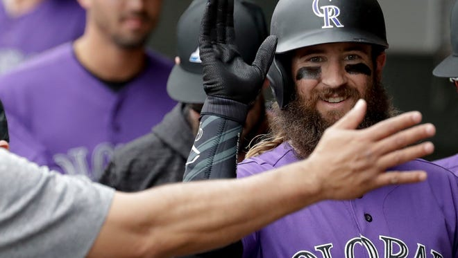 Colorado Rockies' Charlie Blackmon celebrates in the dugout after his home run against the Oakland Athletics during the first inning of a spring training baseball game in Mesa, Ariz., Thursday, March 22, 2018. (AP Photo/Chris Carlson)