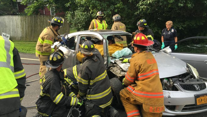 Emergency personnel work at the scene of single-car accident in the Town of Milan on Thursday.