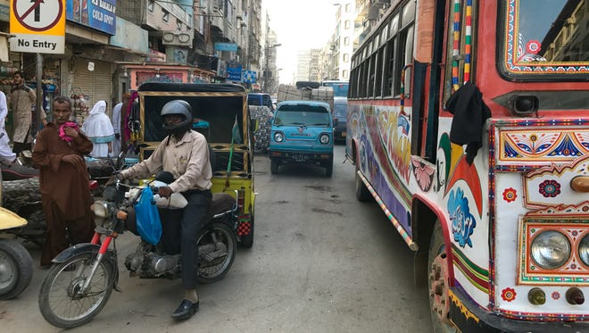"Traffic at a standstill at a crowded road in Karachi, Pakistan May 2017. The public bus (right) features ""truck art,"" an indigenous style of art featuring floral patterns, vibrant colors and stamped metal designs."