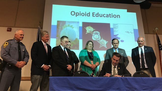 Gov. Ralph Northam signs Senate Bill 399 during an opioid awareness program at Eastern Shore Community College, in Melfa, last week. The landmark legislation aims to give Virginia cities and counties another tool to fight future deaths caused by the opioid epidemic.
