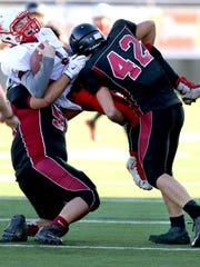 Perrydale's Keenan Bailey (42) and Alex Hawes (55) bring down Dufur quarterback Bailey Keever (1) during the OSAA Class 1A state semifinals, Saturday, November 21, 2015, at Hillsboro Stadium in Hillsboro, Ore. Dufur won the game 42-38. Dufur won the game 42-38.