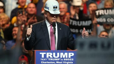 Republican Presidential candidate Donald Trump models a hard hat in support of the miners during his rally at the Charleston Civic Center on Thursday in Charleston, W. Va. Trump became the Republican presumptive nominee following his landslide win in Indiana on Tuesday.