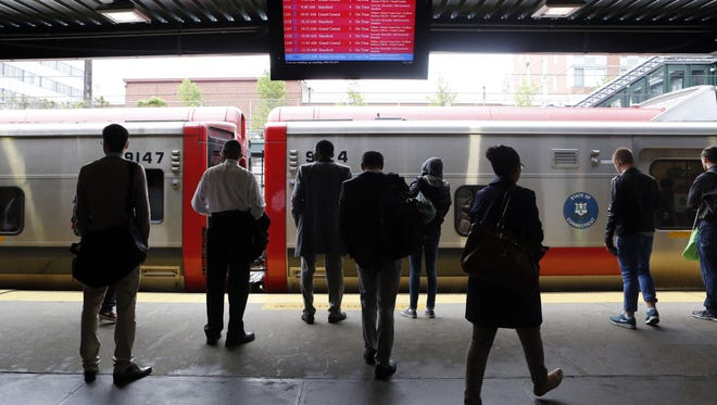 Commuters approach a delayed New York City bound train, May 16, 2014, at the New Rochelle station.