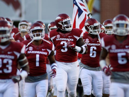 FILE - In a Saturday, Oct. 8, 2016 file photo, Arkansas' McTelvin Agim smiles as he runs out with the team before the start of an NCAA college football game against Alabama in Fayetteville, Ark. Agim started the final five games for the Razorbacks last season as a true freshman. Now 6-3 and 286 pounds, many expect him to use his quickness and power to approach an all-SEC level this season. (AP Photo/Samantha Baker, File)