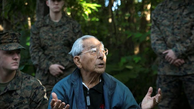 Takejiro Higa, a former member of the U.S. Army's Military Intelligence Service, talks to U.S. Marines during a visit in December 2014 to a cave where he coaxed some 200 Japanese civilians and soldiers to safety during the Battle of Okinawa in April-June 1945. The cave is located on what is now the Marines's Futenma Air Base.