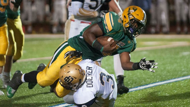 Grosse Pointe North's Jared Jordan dives for extra yardage over Grosse Pointe South's Jack Doerer in a Week 5 matchup.