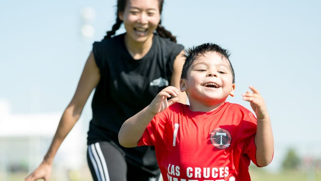 Allen Lawson, 4, of Las Cruces, runs away from Susie Wu while playing together during Las Cruces Timbers Football Club's soccer camp for special needs kids at the High Noon Soccer Fields on Saturday, August 26, 2017. Twelve coaches have completed TOPSOCCER certification which is USA soccers outreach program for kids with special needs.