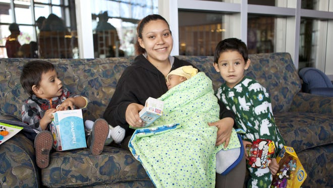 Alejandra Garcia poses with her three sons – 4-year-old Xavier, 2-year-old Elijah and 7-week-old Geevonnie – after the children received their Christmas presents.