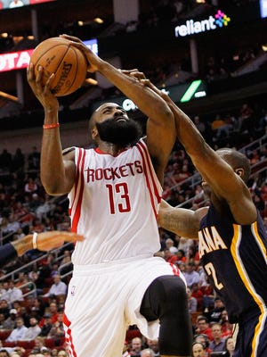 Houston Rockets guard James Harden (13) is  fouled by Indiana Pacers guard Rodney Stuckey (2) as he drives to the basket during the first half of an NBA basketball game Monday, Jan. 19, 2015, in Houston. (AP Photo/Bob Levey)
