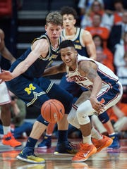 Michigan forward Moritz Wagner (13) and Illinois guard Te'Jon Lucas (3) eye a loose ball during the second half of U-M's 85-69 loss Wednesday in  Champaign, Ill.